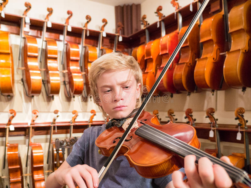 弹一把小提琴的男孩小提琴手在音乐商店 免版税库存图片