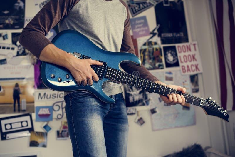 弹一把电吉他的十几岁的男孩在卧室爱好和mu 免版税库存照片