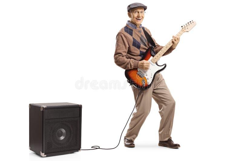 弹一把电吉他的快乐的老人被塞住入放大器 图库摄影