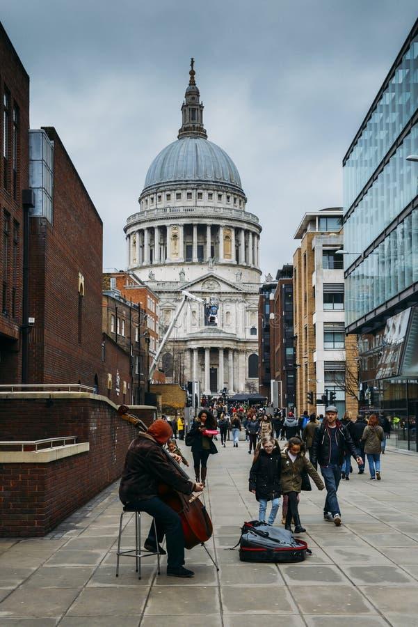 弹一把颠倒的大提琴的音乐街道执行者俯视圣保罗` s大教堂在伦敦,英国,英国 免版税库存照片
