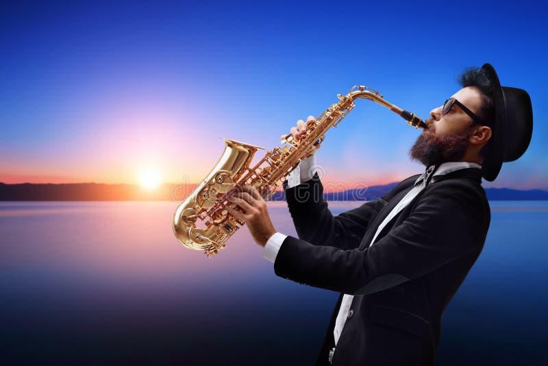 弹一支萨克斯管用日落和水的男性爵士乐音乐家 免版税库存图片