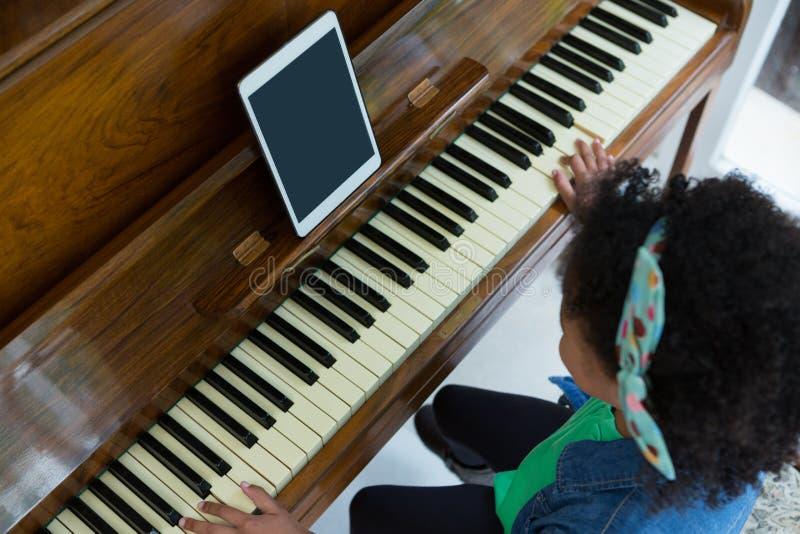弹与数字式片剂的女孩钢琴 免版税图库摄影