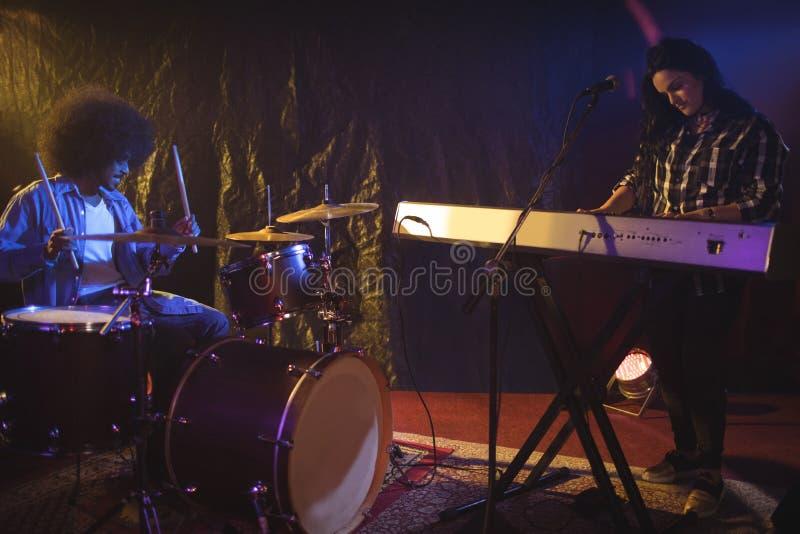 弹与鼓手的音乐家钢琴夜总会的 免版税库存照片