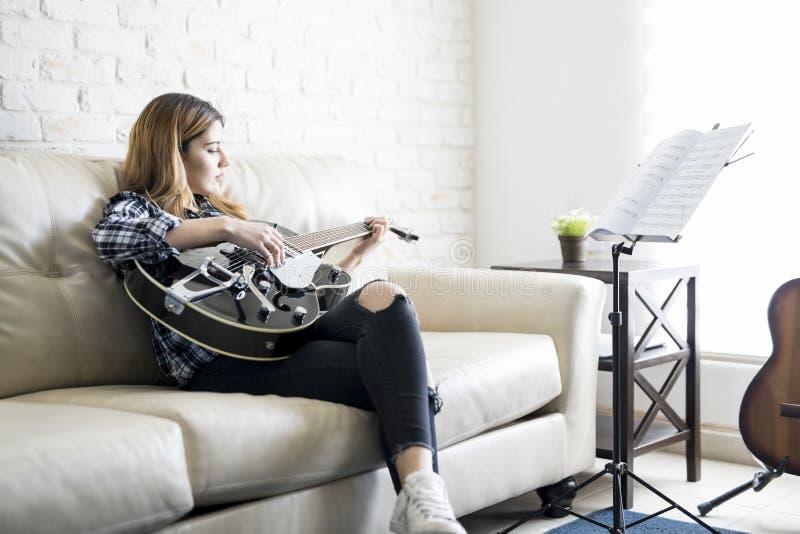 弹从音乐纸张的妇女吉他 库存照片