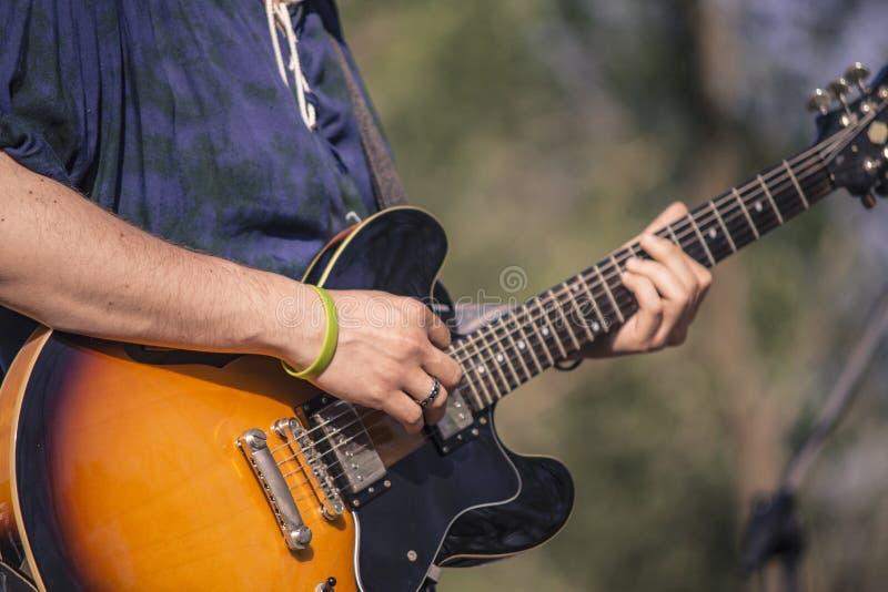 弹他的电吉他的摇摆物的细节 免版税图库摄影