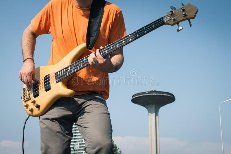 弹低音吉他的一位年轻音乐家的细节 免版税图库摄影