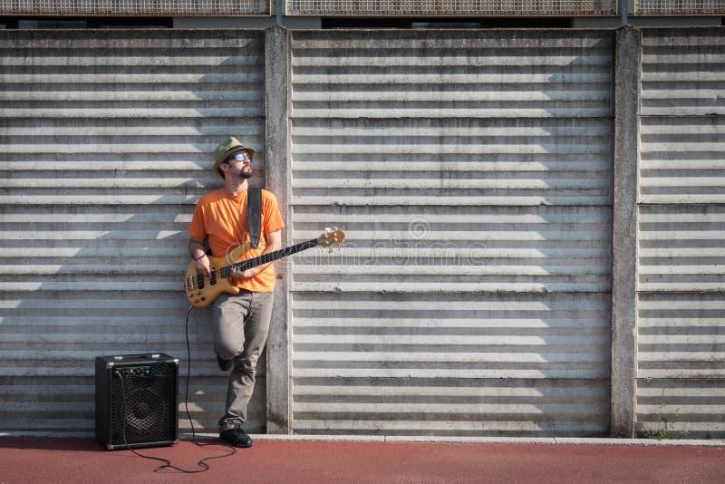 弹低音吉他的年轻音乐家 库存图片