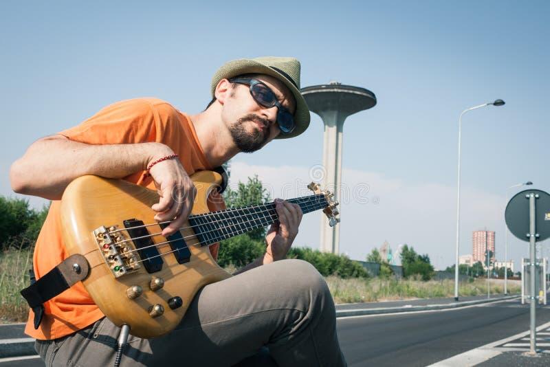 弹低音吉他的年轻音乐家 免版税库存图片