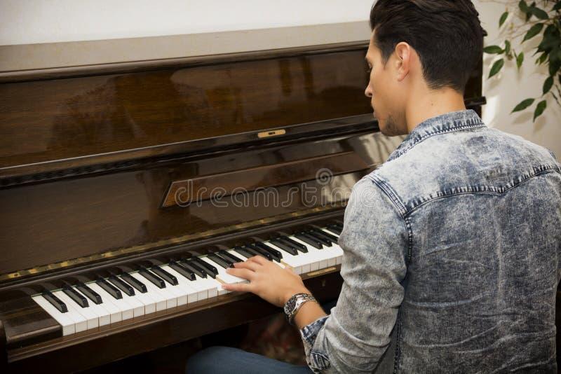 弹古典大钢琴的年轻英俊的男性艺术家 库存图片