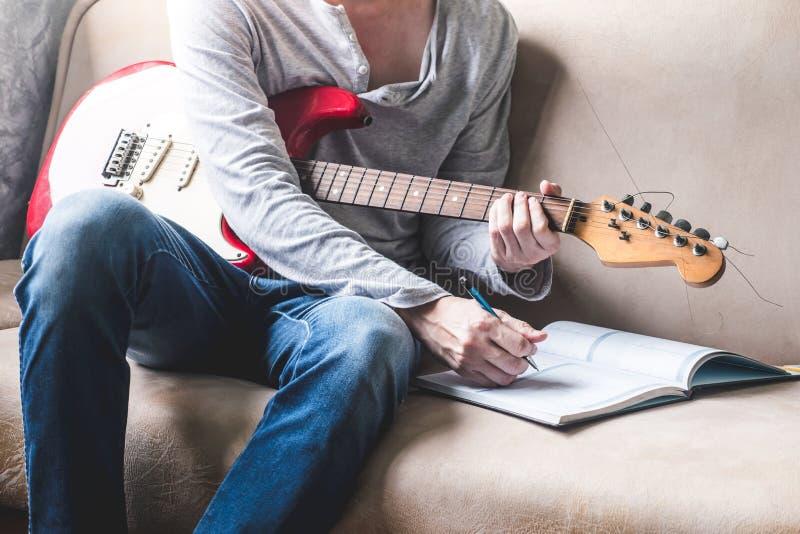 弹吉他和在家写一些数据的偶然年轻人在笔记本在沙发 免版税库存照片