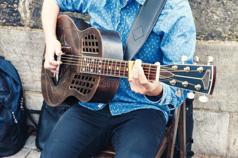 弹吉他的一个人日间坐街道 库存图片