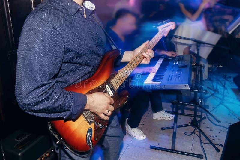 弹吉他的人在婚礼聚会 活音乐家的带执行 库存图片