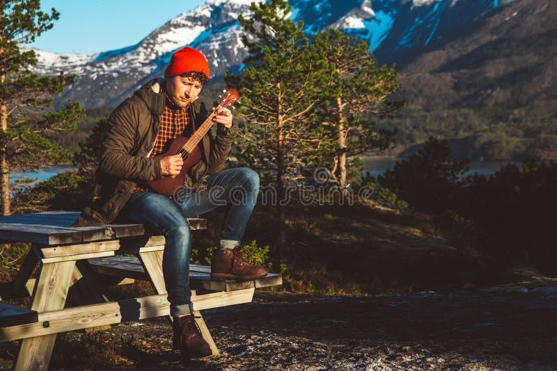 弹吉他的人坐一张木桌以山,森林和湖为背景,穿衬衣和  库存图片
