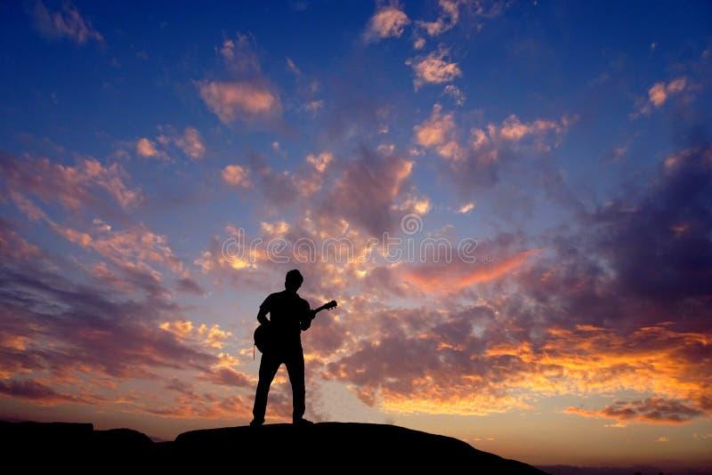 弹吉他的剪影无法认出的吉他弹奏者在岩石顶部在日落期间 免版税库存照片