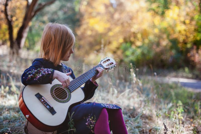 弹吉他的女孩在秋天森林里 免版税库存图片
