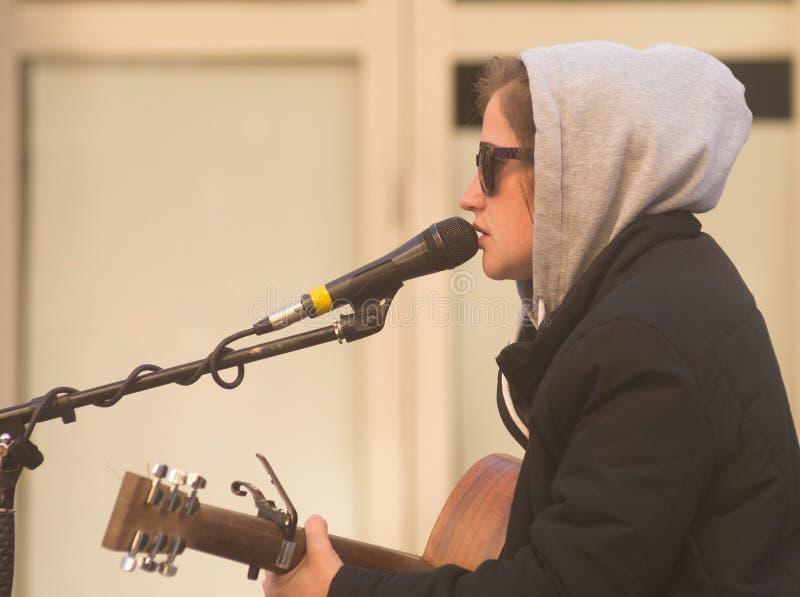 弹吉他的女性卖艺人 免版税图库摄影
