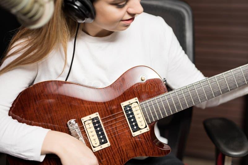 弹吉他的女歌手在电台 免版税库存图片