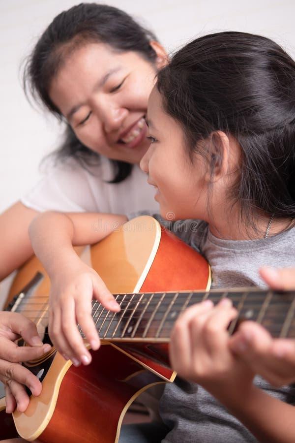 弹吉他的妈妈和女儿 免版税库存照片