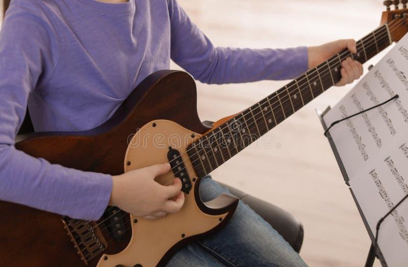 弹吉他的孩子在音乐课 学会笔记 免版税库存照片