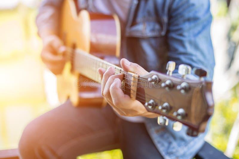 弹吉他的年轻行家人对放松在他的假日,享用与自然和新鲜空气 免版税库存图片