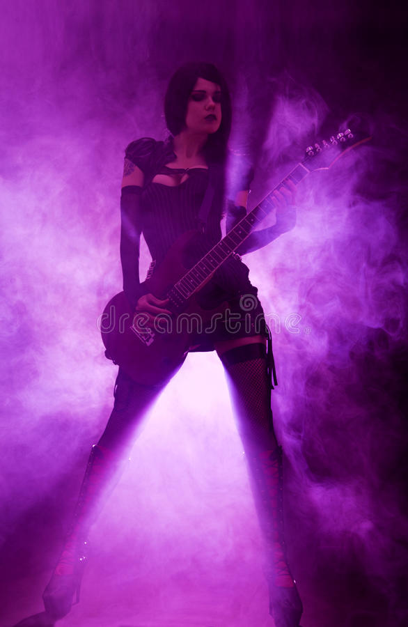 弹吉他的性感的妇女 免版税库存图片
