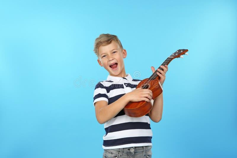 弹吉他的情感小男孩画象  库存图片