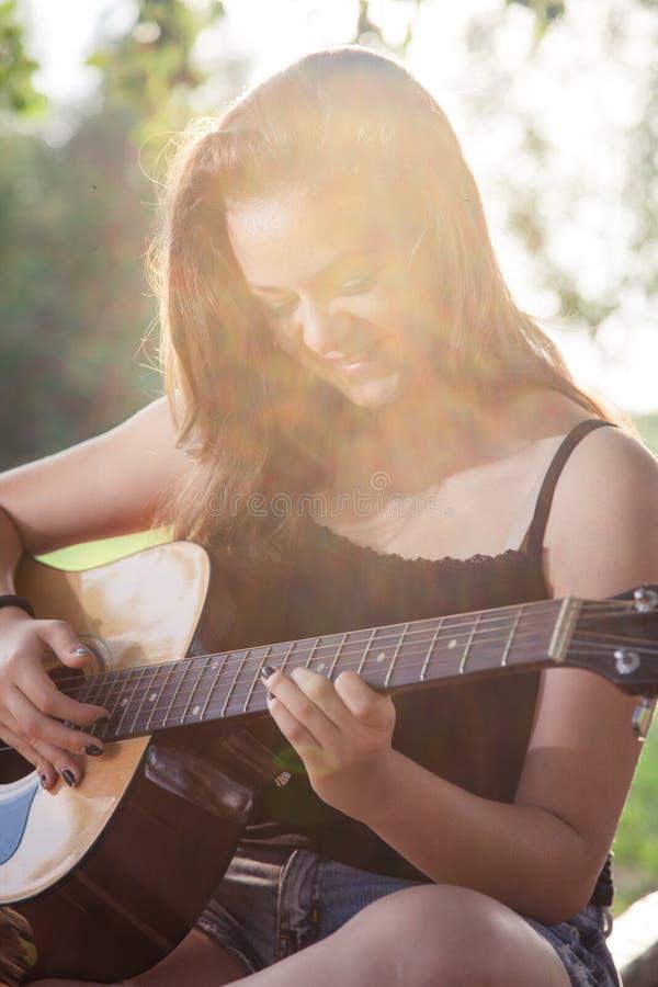 弹吉他的愉快的十几岁的女孩 免版税库存图片