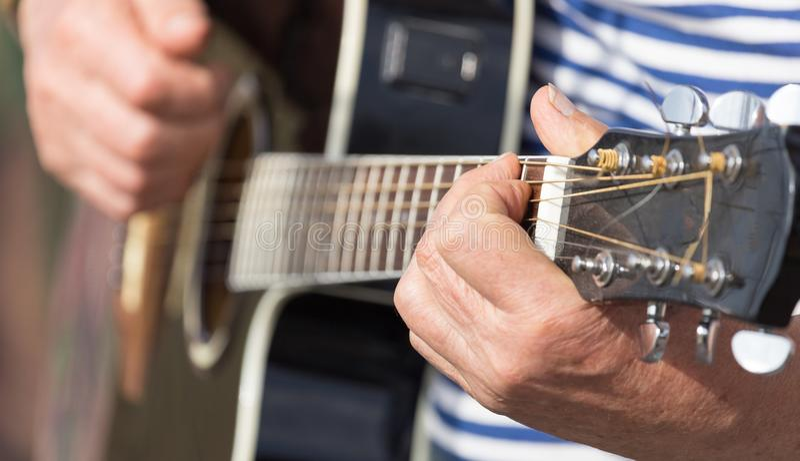 弹吉他的手人 免版税库存照片