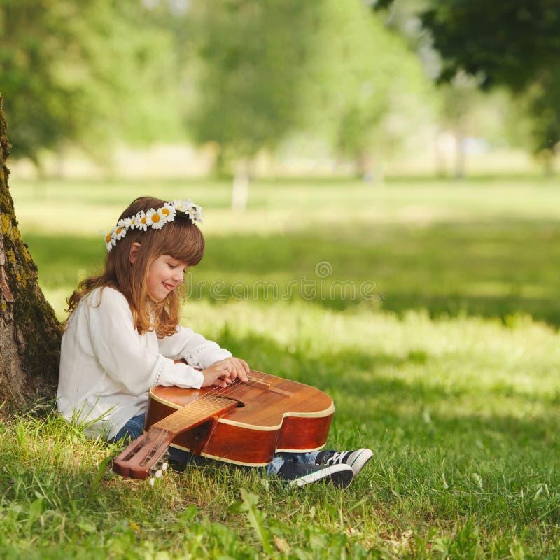 弹吉他的男孩和女孩在夏天公园 免版税库存图片