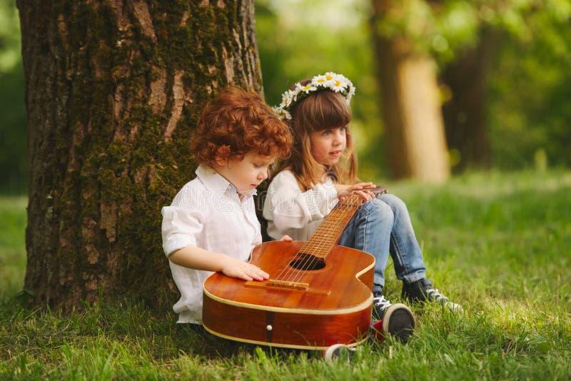 弹吉他的男孩和女孩在夏天公园 库存图片