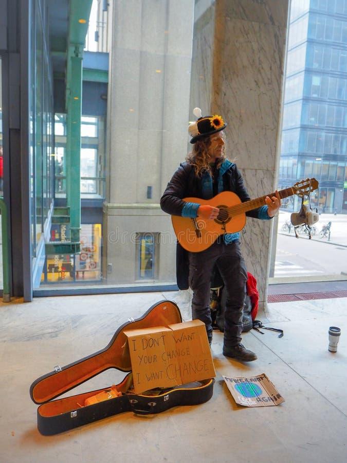 弹吉他的男性街道艺术家在气候变化抗议集会期间作为开始行动 免版税库存照片