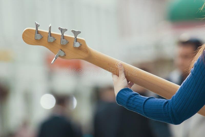 弹吉他的街道音乐家的女性手 免版税库存照片