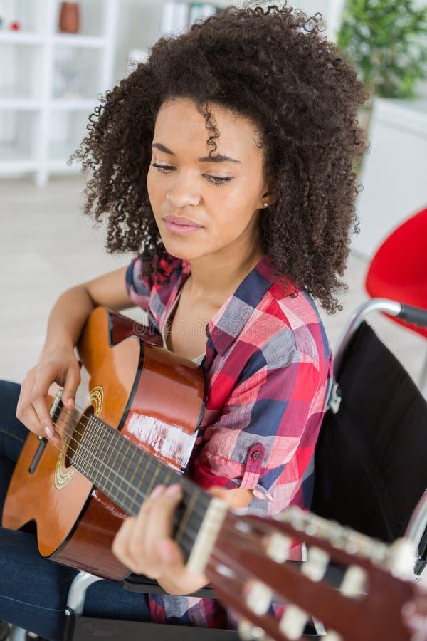 弹吉他的轮椅的妇女 免版税库存照片