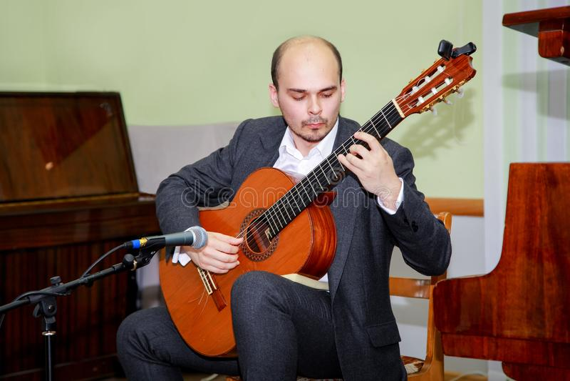 弹吉他的音乐会执行者 在舞台的年轻吉他弹奏者戏剧 免版税库存照片