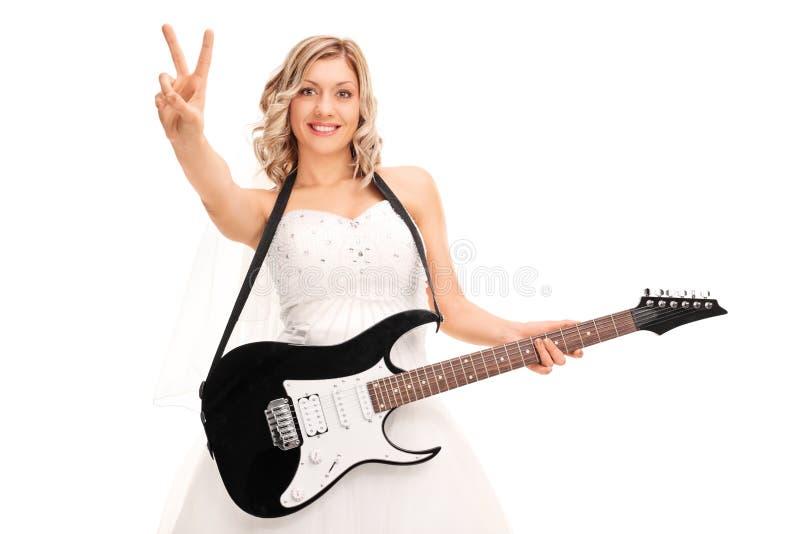 弹吉他和做和平标志的新娘 免版税图库摄影