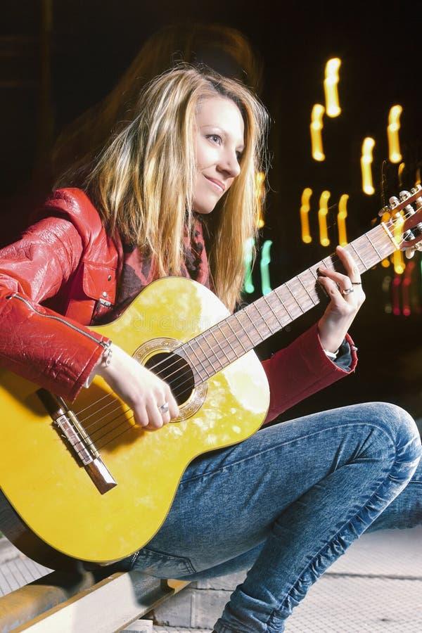 弹吉他外面在街道上的愉快的微笑的白种人白肤金发的女孩 闪光和卤素的组合 免版税图库摄影