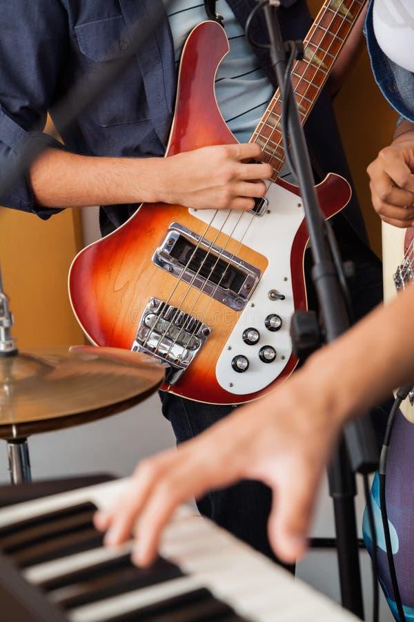 弹吉他的乐队成员在录音室 库存图片