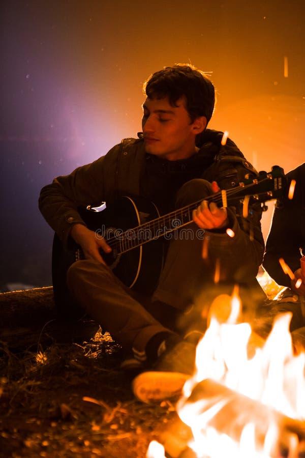 弹吉他的人在满天星斗的天空的背景的一个营火附近 库存图片