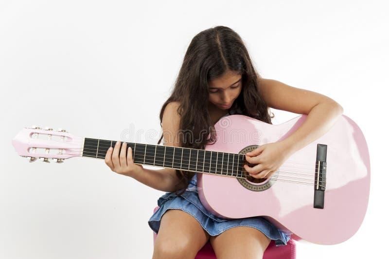 弹吉他的女孩和唱歌 免版税库存照片