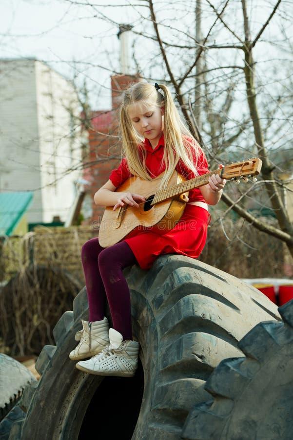 弹吉他的女孩坐轮胎 库存照片