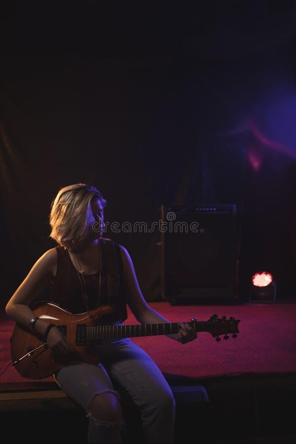 弹吉他的女性吉他弹奏者,当坐阶段时 免版税库存图片