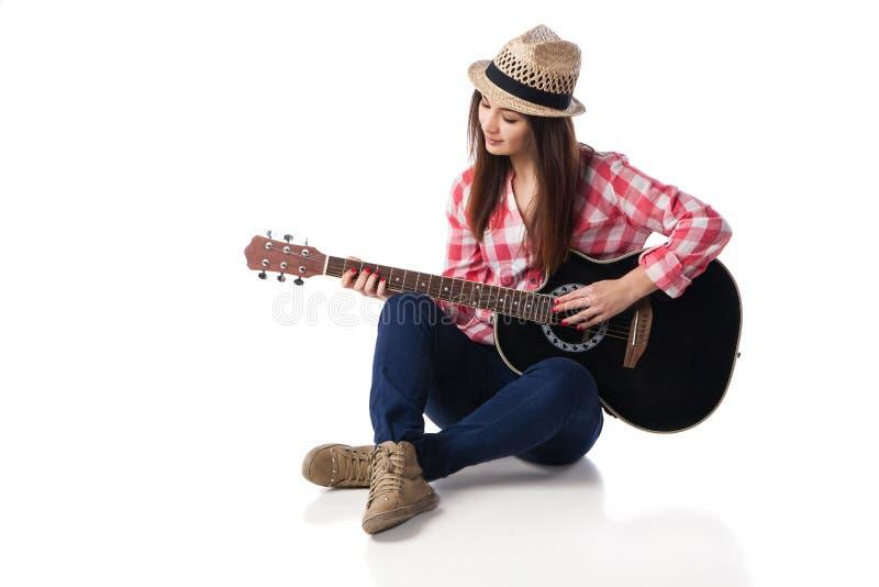 弹吉他的妇女音乐家坐地板 免版税库存照片