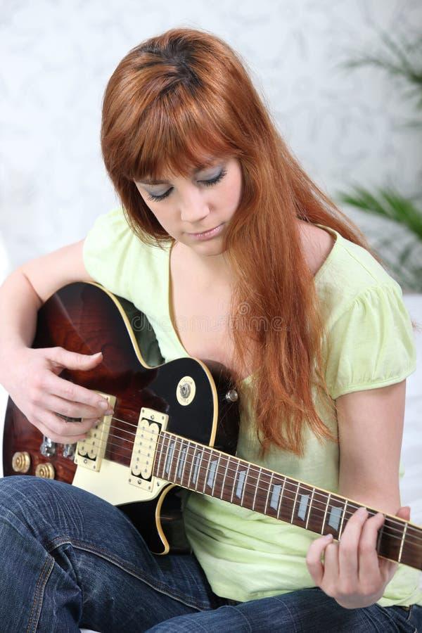 弹吉他的姜头发的女孩 库存照片