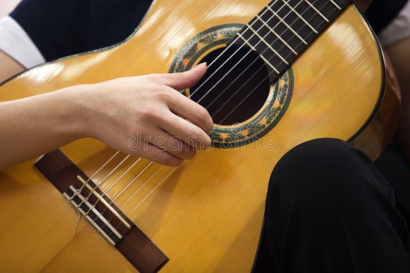 弹吉他的手女孩 免版税图库摄影