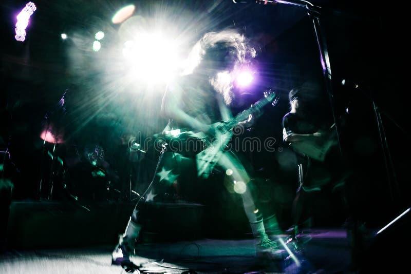 弹吉他的摇滚明星在音乐音乐会 免版税图库摄影