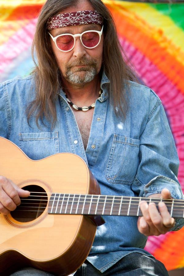 弹吉他的有胡子的中年嬉皮人 免版税库存图片