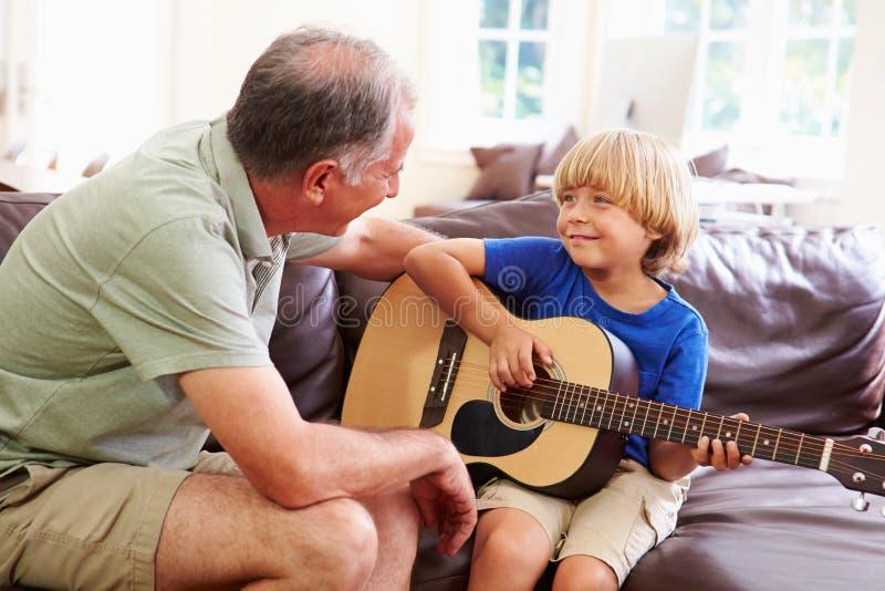 弹吉他的祖父教的孙子 库存图片