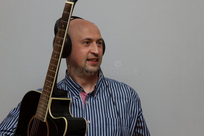 弹吉他的英俊的年轻人和听与耳机的音乐 免版税图库摄影