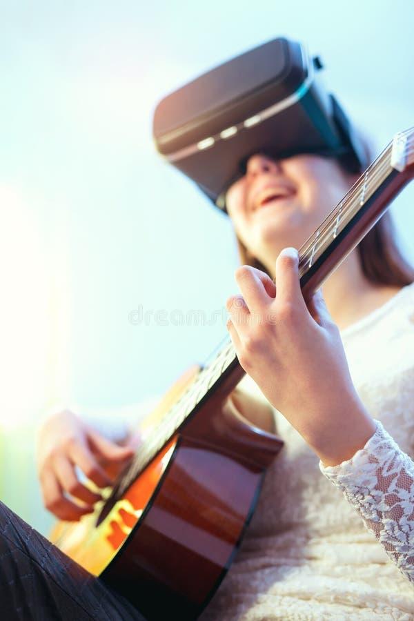 弹吉他的虚拟现实玻璃的愉快的女孩 库存照片