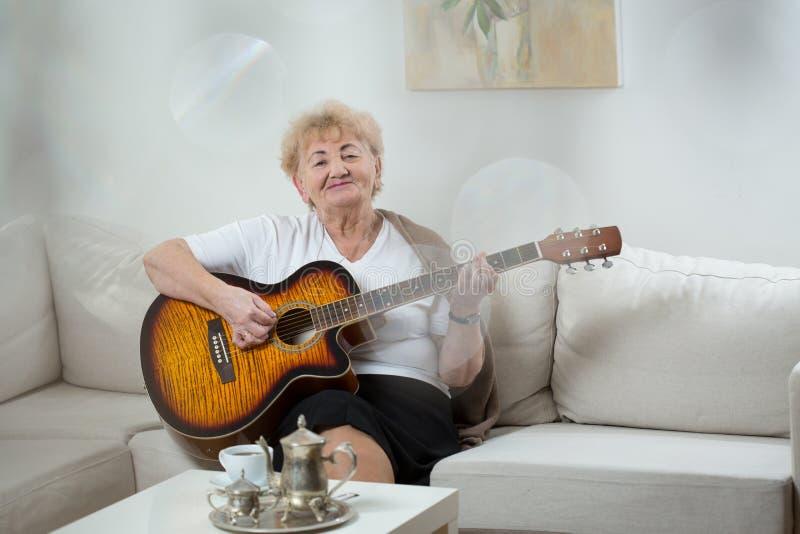 弹吉他的资深妇女 免版税库存照片